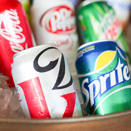 assorted cans of soda in a bucket of ice
