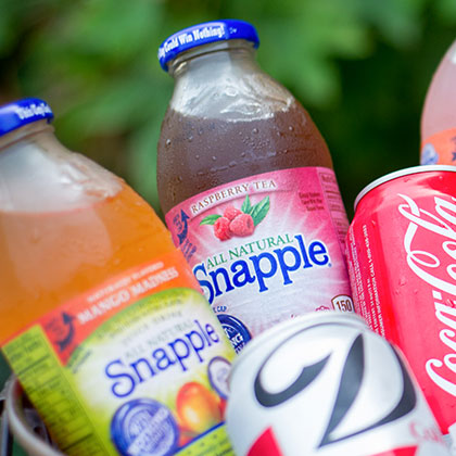 assorted bottles of snapple drink displayed in a bucket of ice
